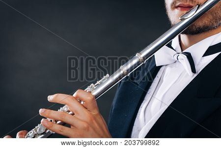 Elegantly Dressed Male Musician Playing Flute
