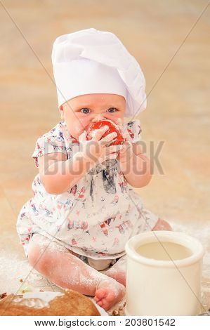 Cute liitle girl in chef's hat sitting on the kitchen floor soiled with flour playing with food, eating tomato, making mess and having fun