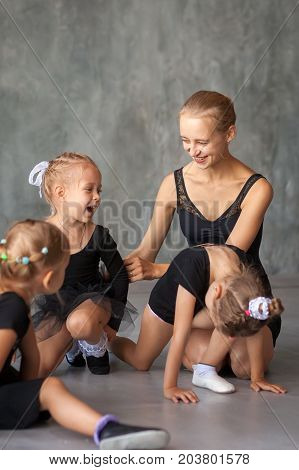 An adult beautiful ballerina in a black dress white pantyhose and pointe shoes sits on the floor and talks with little girls about ballerinas about dances girls laugh and have fun