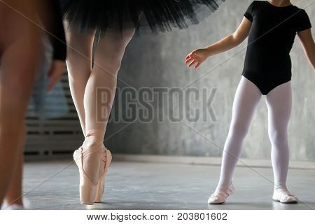 Close-up of an adult beautiful ballerina in a black dress white pantyhose and pointe shoes is dancing and a little girl of a ballerina who is just beginning to study at her