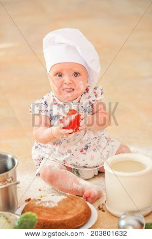 Cute little girl in chef's hat sitting on the kitchen floor soiled with flour playing with food making mess, holding a tomato