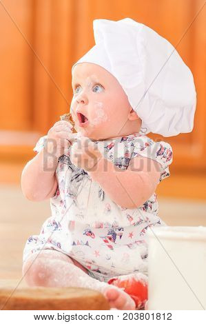 Toddler girl in dress and chef's hat sitting on the kitchen floor soiled with flour playing with food making mess and having fun