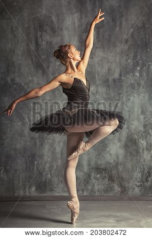Young beautiful woman prima theater in a black festive pack white pantyhose white pointe shoes beautifully dancing russian ballet in a black dance studio