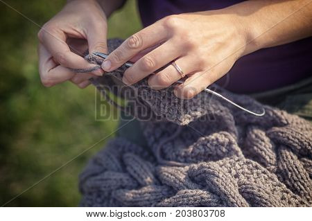 Close-up A young cheerful woman in a purple sweater knits with knitted needles of a natural Italian wool cardigan in the background a green grass side view