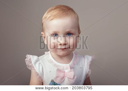 Closeup portrait of cute adorable white blonde Caucasian baby with blue eyes girl looking in camera. Child girl smiling posing in studio on plain light background.