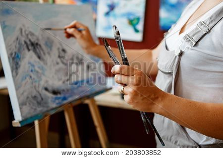 Closeup of young beautiful middle age white Caucasian woman artist drawing painting with acrylic paints on canvas. Female hands holding paintbrushes in art studio. Lifestyle activity hobby concept