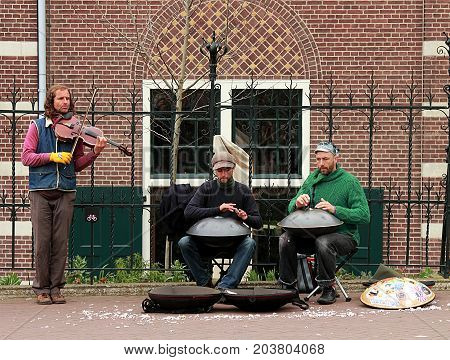 Amsterdam, Netherlands - April 5, 2016: Street musicians with hang drums and violin performing in Amsterdam, Netherland