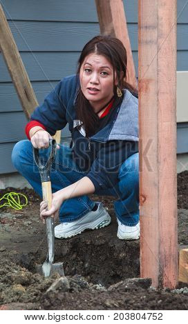 Woman Digs Post Hole For Habitat For Humanity