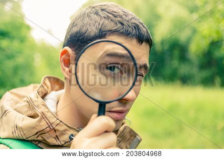 Picture of brunet biologist with magnifying glass in summer forest
