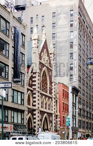 New York USA - 27 September 2016: Buildings located along West 37th Street at Broadway Manhattan including the iconic Roman Catholic Church of the Holy Innocents.