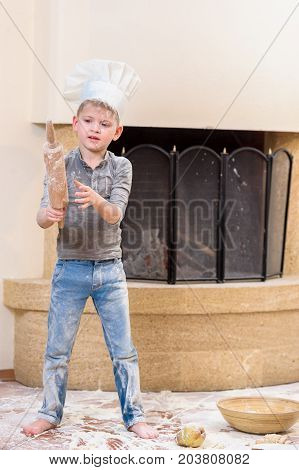 A boy in chef's hat near the fireplace standing on the floor soiled with flour playing with food and roller pin, making mess and having fun
