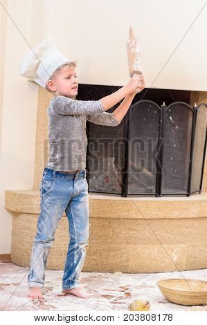 A boy in chef's hat near the fireplace standing on the kitchen floor soiled with flour playing with roller pin, making