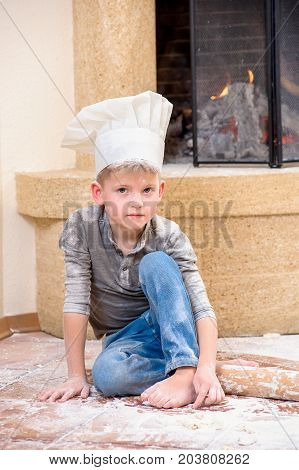 A boy in chef's hat near the fireplace sitting on the floor soiled with flour playing with food making mess
