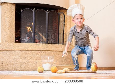 A cute boy in chef's hat near the fireplace sitting on the kitchen floor soiled with flour playing with food making mess and having fun