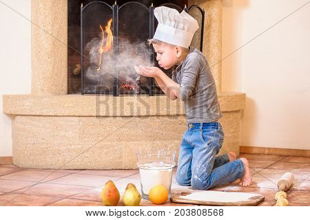 A boy in chef's hat near the fireplace sitting on the kitchen floor soiled with flour playing with food making mess and having fun