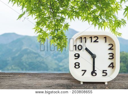 Closeup white clock for decorate show half past ten o'clock or 10:30 a.m. on blurred mountain view background