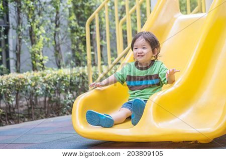 Closeup asian kid play a slider at the playground background