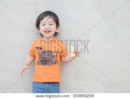 Closeup happy asian kid with crispy corn snack in his hand on marble stone wall textured background with copy space
