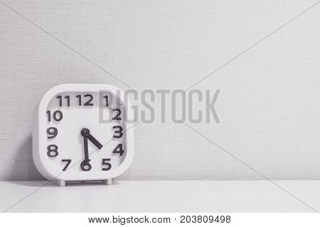 Closeup white clock for decorate show half past four o'clock or 4:30 p.m. on white wood desk and cream wallpaper textured background in black and white tone with copy space