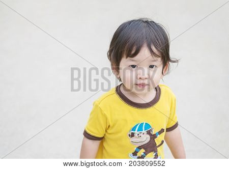 Closeup cute asian kid stand on blurred concrete street textured background with copy space