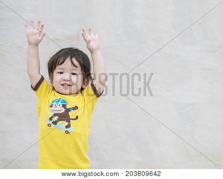 Closeup happy asian kid with put his hand up action on marble stone wall textured background with copy space