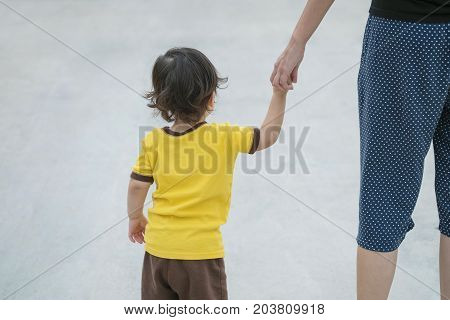 Closeup cute asian kid walk in the hand of parent on concrete floor textured background