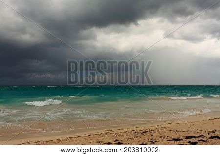 Rainy tropical storm coming from the atlantic ocean to the caribbean shore. Gloomy dark cloudy sky, turbulent sea waves. Empty overcast beach just before the wild rainfall