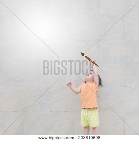 Closeup cute asian kid use paintbrush point to copy space at the marble stone wall textured background