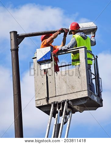 Electicians are fixing a street light in the city