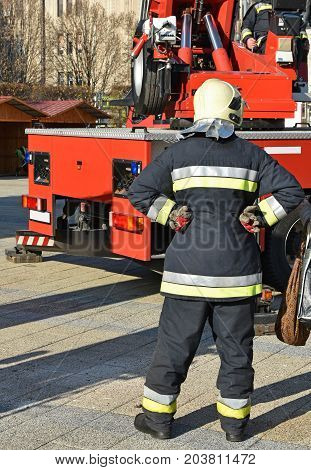Firefighter stands next to a crane outdoor