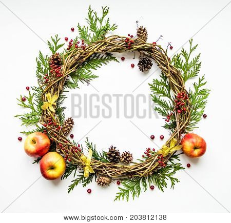 Festive wreath of grape vines with apples thuja branches rowanberries cranberries and cones. Christmas DIY wreath. New Year round wreath decorated with ribbons on white background. Flat lay top view