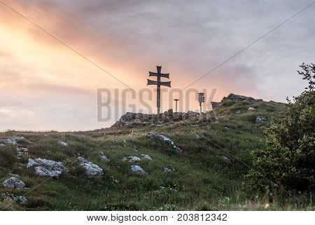 Klak hill eith cross mountain meadow and limestone stones in Mala Fatra mountains in Slovakia during sunset with colorful sky