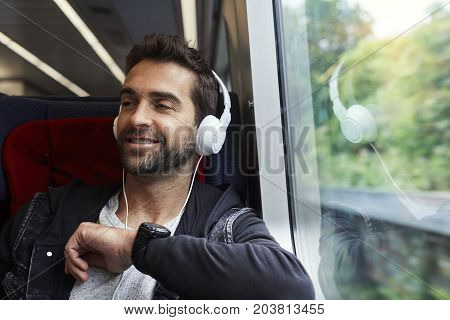 Dude with phones on train looking away and smiling