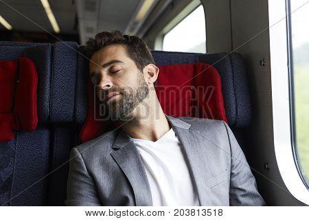 Bearded dude in suit jacket asleep on train
