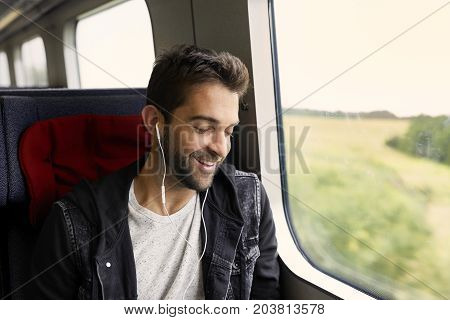 Smiling dude on train listening to music