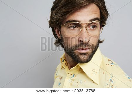 Handsome dude in glasses and yellow shirt studio