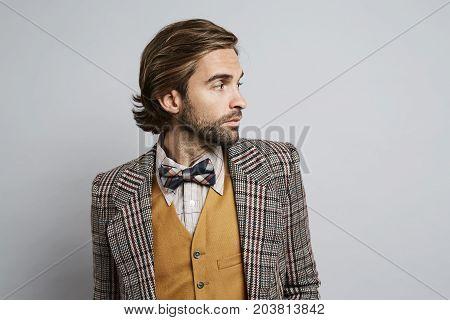 Geek guy in jacket and bow tie looking away