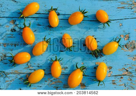 yellow small tomatoes on a blue wooden surface