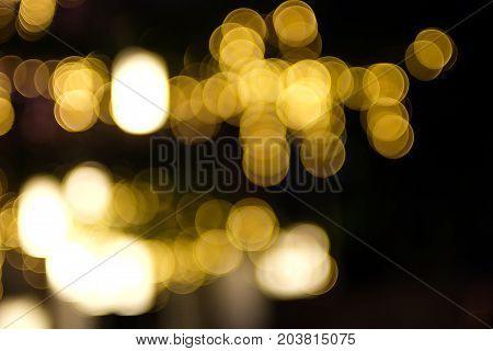 Blury gold bokeh on black background in night.