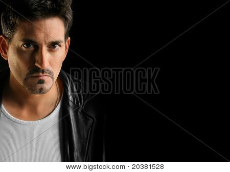Tough looking man wearing black leather jacket against black background with lots of copy space