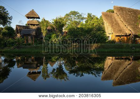 June 6 2017 Puerto Misahualli: eco lodge built from bamboo in the jungle reflecting into water at sunset