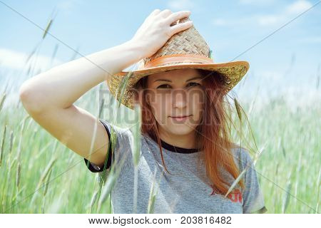Girl in a wheat field. Portrait of a girl in a straw hat. Portrait of woman in blue dress and straw hat against a background of wheat field