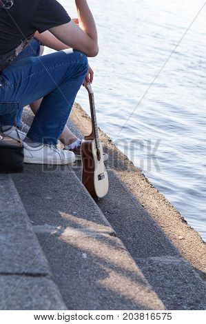 outdoor recreation by the water man with a guitar. Man and guitar on the river. The concept of freedom and serenity. old style