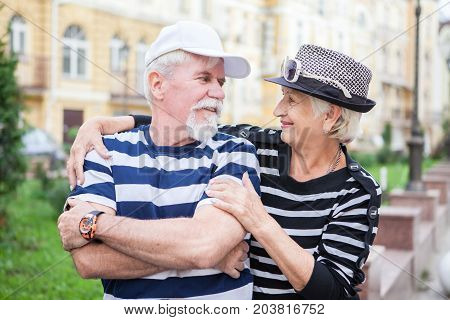 Happy mature man and woman leaned against each other. Mature man and woman smiling leaning against each other