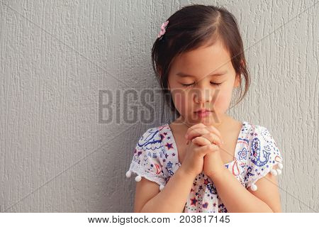 asian little girl praying with eyes closed