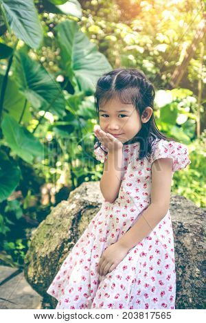 Adorable Asian Child Smiling And Relaxing At Park With Sunlight, Travel On Vacation.