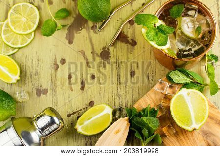Refreshing moscow mule cocktail in copper mug with mint and lime on wet wooden table. Space for text