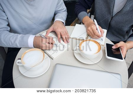 Two Cheerful Asian Business People Discussing With Documents