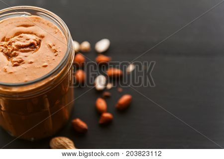 Peanut Butter On A Table In A Glass Jar With Peanuts Around