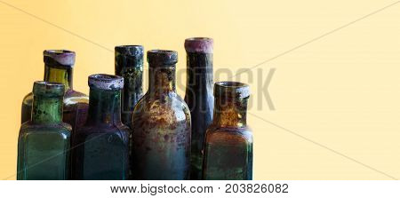 Vintage bottles close-up. Colorful dirty glass flacon set. Soft yellow orange background, shallow depth of field. copy space